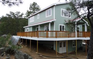 Shown here is a custom off-grid home with second story wrap-around wood deck and solar panels on the ground.