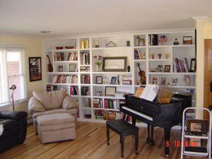 built-in wall length music room white bookshelves