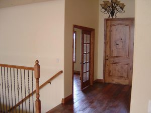 this shows the interior entryway of a custom home with wood floors.