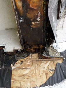 This shows a close-up of exposed water damage on the exterior of a house.
