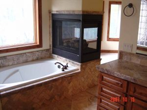 This is a beautiful tile-work tub and fireplace in a remodeled bathroom.