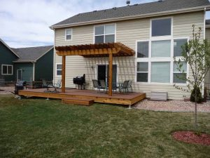 This is the back of a custom home with wood deck and pergola.
